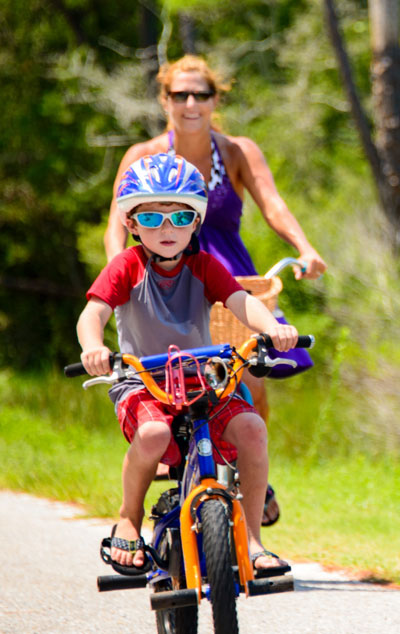 Woman on bike behind child on bike.