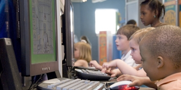young students sitting in view of computer screen